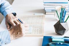 Hombre en libro de lectura azul de la camisa en lugar de trabajo elegante moderno con los materiales de oficina y libros, concept imagen de archivo