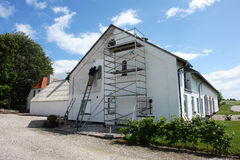 Hombre en los andamios que pintan una casa imagenes de archivo
