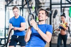 Hombre en los anillos que hacen ejercicio de la aptitud en gimnasio imagen de archivo libre de regalías
