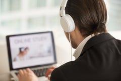 Hombre en los auriculares que miran la pantalla del ordenador portátil, visión trasera fotografía de archivo libre de regalías