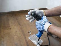 Hombre en los guantes que se preparan para la renovación, poniendo en un poco de broca Concepto de reparaciones en la casa imagenes de archivo