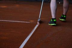 Hombre en los pantalones cortos que limpian líneas del campo de tenis Fotografía de archivo libre de regalías