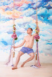Hombre en los pantalones que se sientan en el oscilación de madera con las cuerdas imágenes de archivo libres de regalías