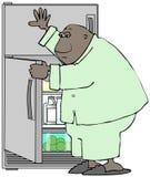 Hombre en los pijamas que atacan el refrigerador Foto de archivo
