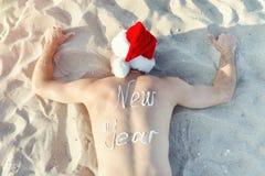 Hombre en los sombreros de Papá Noel con el Año Nuevo de la inscripción en la mentira trasera en la arena Visión desde arriba Fotografía de archivo libre de regalías