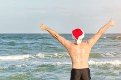 Hombre en los sombreros de Papá Noel con el Año Nuevo de la inscripción en la parte posterior en la playa Pulgares para arriba Vi Imagenes de archivo