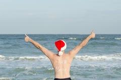 Hombre en los sombreros de Papá Noel con el Año Nuevo de la inscripción en la parte posterior en la playa Pulgares para arriba Vi Foto de archivo