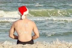 Hombre en los sombreros de Papá Noel con el Año Nuevo de la inscripción en la parte posterior en la playa Visión posterior Imágenes de archivo libres de regalías