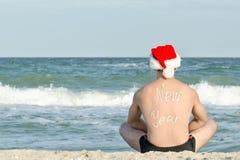 Hombre en los sombreros de Papá Noel con el Año Nuevo de la inscripción en la parte posterior en t Imagen de archivo libre de regalías