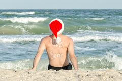 Hombre en los sombreros de Papá Noel con el Año Nuevo de la inscripción en la parte posterior en t Fotografía de archivo