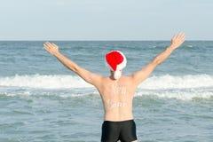 Hombre en los sombreros de Papá Noel con el Año Nuevo de la inscripción en la parte posterior en t Imagenes de archivo