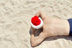 Hombre en los sombreros de Papá Noel que mienten en la arena Visión superior Imágenes de archivo libres de regalías