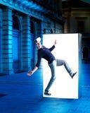 Hombre en los vidrios de la realidad virtual que salen de un cartel de la calle fotografía de archivo