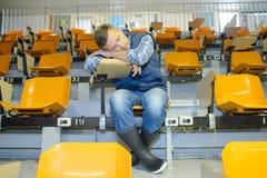 Hombre en los wellingtons dormidos en el escritorio Fotografía de archivo libre de regalías