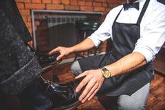 Hombre en los zapatos que se sientan delante de trabajador Imagenes de archivo