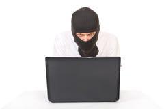 Hombre en máscara negra con el ordenador que mira la cámara fotografía de archivo libre de regalías