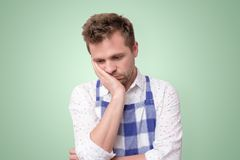 Hombre en mano de la tenencia del delantal w en la mejilla que parece cansada de tareas de hogar imagenes de archivo