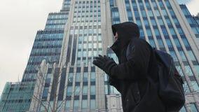Hombre en manos negras del frotamiento de la chaqueta y de la mochila y caminar en la calle de la ciudad almacen de video