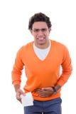 Hombre en necesidad con los problemas del estómago que sostienen el papel higiénico en naranja Imagen de archivo