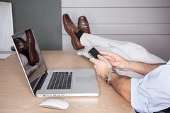 Hombre en oficina con los pies en el escritorio y la computadora portátil imágenes de archivo libres de regalías