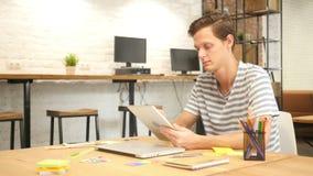 Hombre en oficina usando la tableta de Digitaces, diseñador creativo, agencia almacen de video