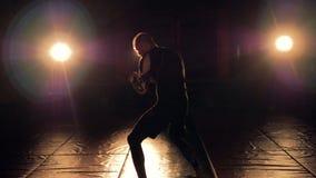 Hombre en oscuridad con los proyectores que entrena al boxeo de la sombra 4K almacen de metraje de vídeo