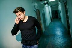 Hombre en pasillo oscuro con el contraluz que habla en el teléfono, salido fuera del cuarto de la oficina Conversación seria Imagenes de archivo