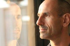 Hombre en pensamiento con la reflexión de la ventana foto de archivo