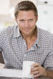 Hombre en periódico y la sonrisa de la lectura de la cocina Imagen de archivo