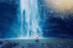 Hombre en piscina en la base de la cascada grande Fotos de archivo