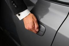 Hombre en puerta de coche de la apertura del smoking Fotos de archivo libres de regalías