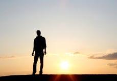 Hombre en puesta del sol Imagenes de archivo