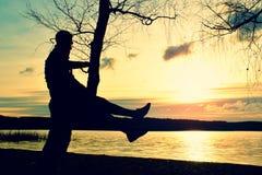 Hombre en árbol La silueta del hombre solitario se sienta en la rama del árbol de abedul en la puesta del sol en la línea de la p Fotografía de archivo