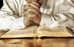 Hombre en rezo profundo sobre su Sagrada Biblia fotos de archivo libres de regalías