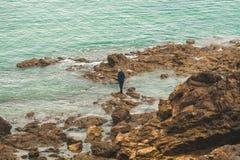 Hombre en rocas en el mar Imagenes de archivo