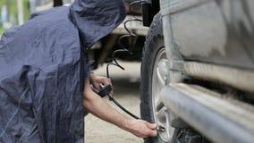Hombre en ruedas de bombeo del impermeable de SUV en el borde de la carretera metrajes