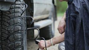 Hombre en ruedas de bombeo del impermeable de SUV en el borde de la carretera almacen de metraje de vídeo