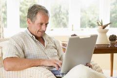 Hombre en sala de estar con la computadora portátil Fotografía de archivo