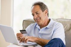 Hombre en sala de estar con la computadora portátil Imagen de archivo libre de regalías