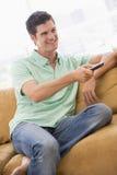 Hombre en sala de estar con teledirigido Imagen de archivo