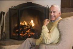 Hombre en sala de estar por la sonrisa de la chimenea Fotos de archivo libres de regalías