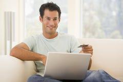 Hombre en sala de estar usando la computadora portátil Imagenes de archivo