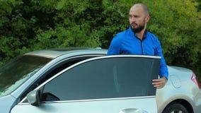 Hombre en salir azul de la camisa del coche metrajes