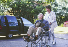 hombre en sillón de ruedas con la enfermera imagenes de archivo