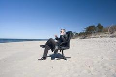 Hombre en silla de la oficina en la playa Fotos de archivo libres de regalías