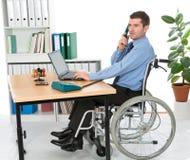 Hombre en silla de ruedas en la oficina Foto de archivo libre de regalías