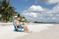 Hombre en silla en la playa de Caribbian Imagenes de archivo