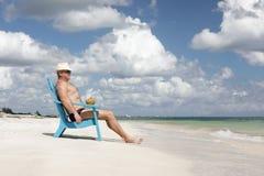 Hombre en silla en la playa de Caribbian Imagen de archivo libre de regalías
