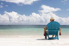 Hombre en silla en la playa de Caribbian Fotos de archivo