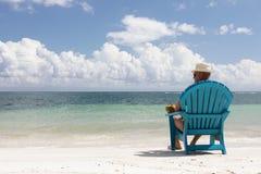 Hombre en silla en la playa de Caribbian Foto de archivo